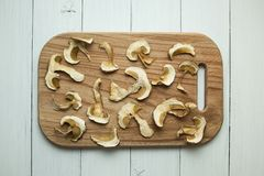 Dried mushrooms on a cutting board. White background stock photos