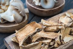 Dried mushrooms and fresh raw oyster mushrooms in craft wooden p. Lates on dark rustic background close-up Stock Photos