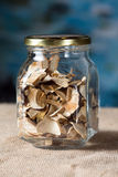 The dried mushrooms in jar. The dried mushrooms in a glass jar on sacking and blue background royalty free stock photos