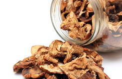 Dried mushrooms pouring out of glass jar. White background Stock Photo
