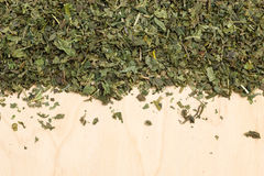 Dried nettle leaves on wooden board with copy space. Healthy food, healing herbs, alternative herbal medicine concept. Border frame of dried herb nettle leaves stock photo