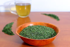 Dried nettle in a wooden bowl with a cup of nettle tea Royalty Free Stock Images