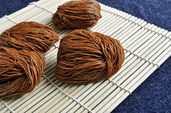 Dried noodles on bamboo mat. Pieces of dried noodles rest on a bamboo mat Royalty Free Stock Photography