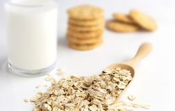Dried oat in spoon and oatmeal cookies on the white table. Its are a nutrient-rich food associated with protein and fiber stock photos