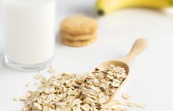 Dried oats in spoon and oatmeal cookies on the white table. Its are a nutrient-rich food associated with protein and fiber stock images