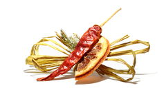 Dried orange and chili pepper isolated on white. A slice of dried orange and a chili pepper with a yellow ribbon isolated on white background stock photos