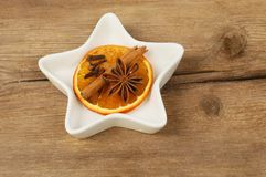 Orange and spices. Dried orange, cinnamon,star anise and cloves in a star shaped dish on old rustic wood royalty free stock photography