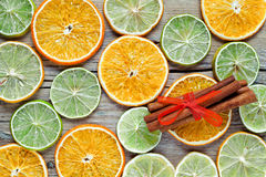 Dried orange, lemon slices and cinnamon sticks on wooden table. Stock Photos