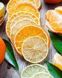 Dried orange and lemon slices, ripe tangerines on old table. Stock Photos