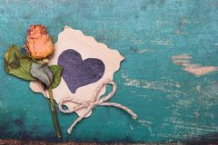 Dried orange roses and heart drawing on wooden background,. Copy space royalty free stock photo