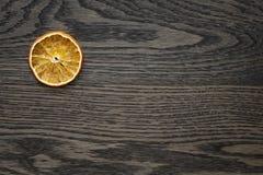 Dried orange slice on dark oak table Stock Photography