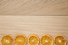 Dried orange slices on natural oak table Stock Photography