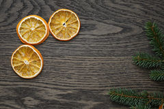 Dried orange slices and spruce twig on dark oak table Stock Photo