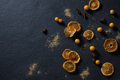 Dried orange with star anise and golden berries on black background. Overhead of dried orange with star anise and golden berries on black background royalty free illustration