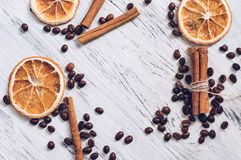 Dried oranges of coffee and cinnamon on a white wooden surface, top view. stock image
