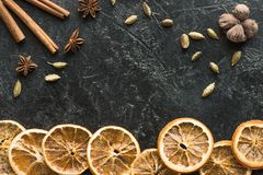 Dried oranges with seeds and carnation. Top view of dried oranges with seeds and carnation on a dark grungy surface stock image