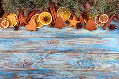 Dried oranges, star anise, cinnamon sticks and gingerbread on a blue wooden background -- Christmas background Royalty Free Stock Images