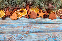 Dried oranges, star anise, cinnamon sticks and gingerbread on a blue wooden background -- Christmas background Royalty Free Stock Photo