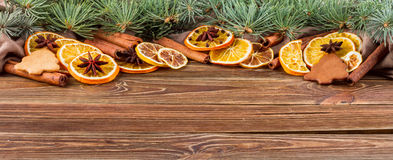 Dried oranges, star anise, cinnamon sticks and gingerbread on a wooden background -- Christmas background, banner Stock Image