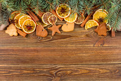 Dried oranges, star anise, cinnamon sticks and gingerbread on a wooden background -- Christmas background Stock Photo