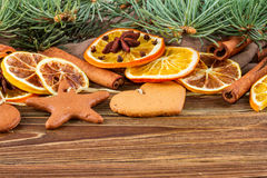 Dried oranges, star anise, cinnamon sticks and gingerbread on a wooden background -- Christmas background Royalty Free Stock Photography