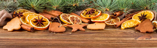 Dried oranges, star anise, cinnamon sticks and gingerbread on a wooden background -- Christmasbackground, banner Stock Photography