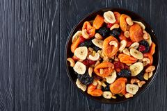 Dried organic Fruits and Nut Mix, flatlay. Dried organic Fruits and Nut Mix - banana slices, apricots, raisins, prunes, cherries and cashew on a black plate on a royalty free stock photography