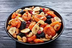 Dried organic Fruits and Nut Mix, flatlay. Dried organic Fruits and Nut Mix - banana slices, apricots, raisins, prunes, cherries and cashew on a black plate on a royalty free stock photo