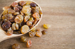 Dried Organic Raisins in a wooden Spoon. Stock Images