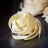 Dried Pappardelle Pasta. Dried pappardelle ribbon pasta over dark slate Royalty Free Stock Images