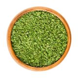 Dried parsley in wooden bowl over white Royalty Free Stock Photos