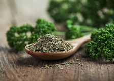 Dried parsley in wooden spoon on wooden Stock Images