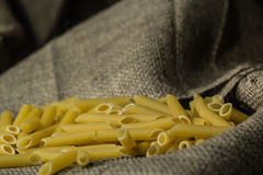 Dried pasta on a burlap cloth with a dark background Royalty Free Stock Photo