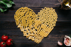 Dried pasta in heart shape top view. Pasta and vegetables on the dark wooden table Stock Photography
