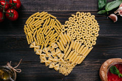 Dried pasta in heart shape top view. Pasta and vegetables on the dark wooden table Stock Image