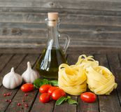 Dried pasta with ingredients for cooking on weathered wooden bac Stock Image