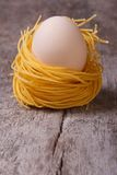 Dried pasta nest with chicken eggs  vertical Royalty Free Stock Image