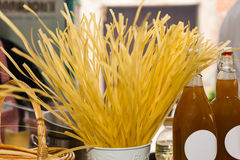 Dried Pasta Noodles Standing Upright on Counter. Close Up Still Life of Fresh Dried Pasta Noodles Standing Upright in Container on Counter with Bottles and Stock Photos