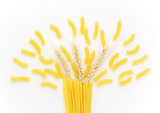 Dried pasta and wheat ears on white background Royalty Free Stock Photography