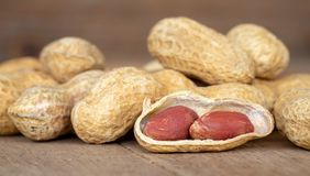 Dried peanuts in shells on peanuts background on wooden table. Concept of snack. Stock Photos