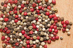 Dried pepper seeds. Image of black, green, white and red pepper on wood background Stock Images