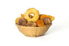 Dried pineapple, apricots and figs in a wicker basket isolated o Royalty Free Stock Images