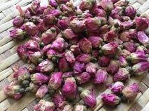 Dried pink Damask rosebuds on bamboo flat basket stock images