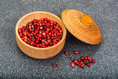 Dried pink pepper peas in a wooden bowl on gray background Royalty Free Stock Images