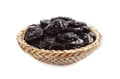 Dried plum in wicker bowl Stock Photo