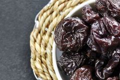 Dried plums in a bowl. Dried plums in a bowl, shallow depth of field Stock Image