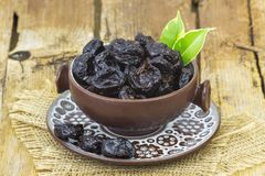 Dried plums in a bowl. On wooden background Stock Photo