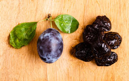 Dried plums and fresh prune fruit on wooden table Royalty Free Stock Photo