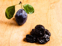 Dried plums and fresh prune fruit on wooden table. Healthy food, good cuisine. Closeup dried plums and fresh prune fruit on wooden rustic table Royalty Free Stock Photo