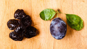 Dried plums and fresh prune fruit on wooden table Stock Photos